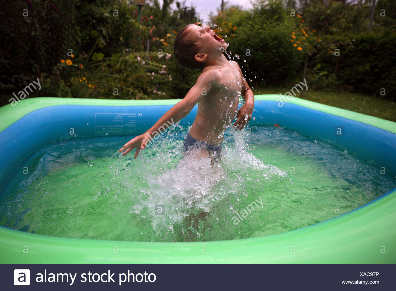 Berlin, Germany, boy rages loudly around in a paddling pool - Stock Image