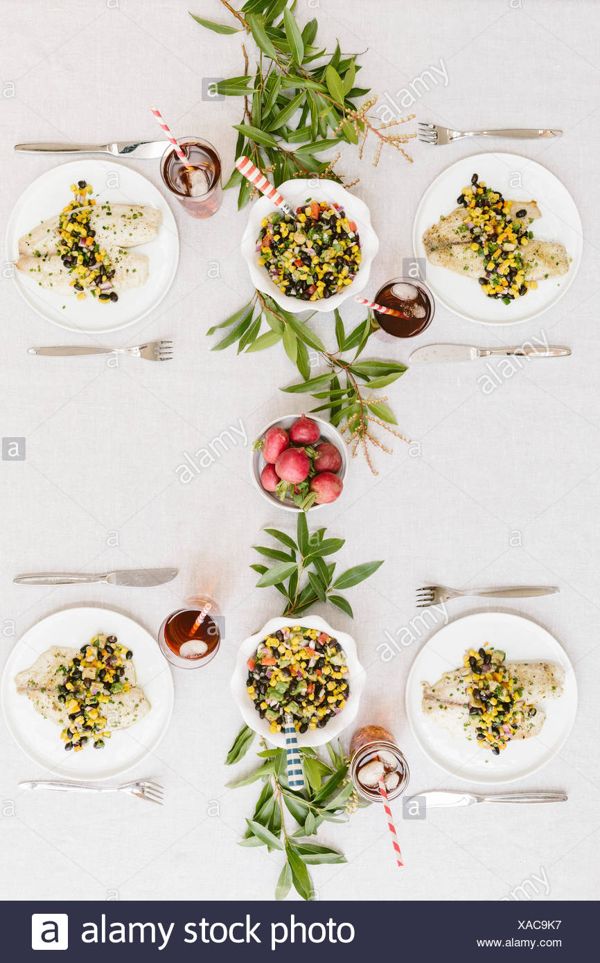 A summery (happy & bright) tablesetting with a portion of Baked Lime and Olive oil tilapia with black bean salsa served on each plate. - Stock Image