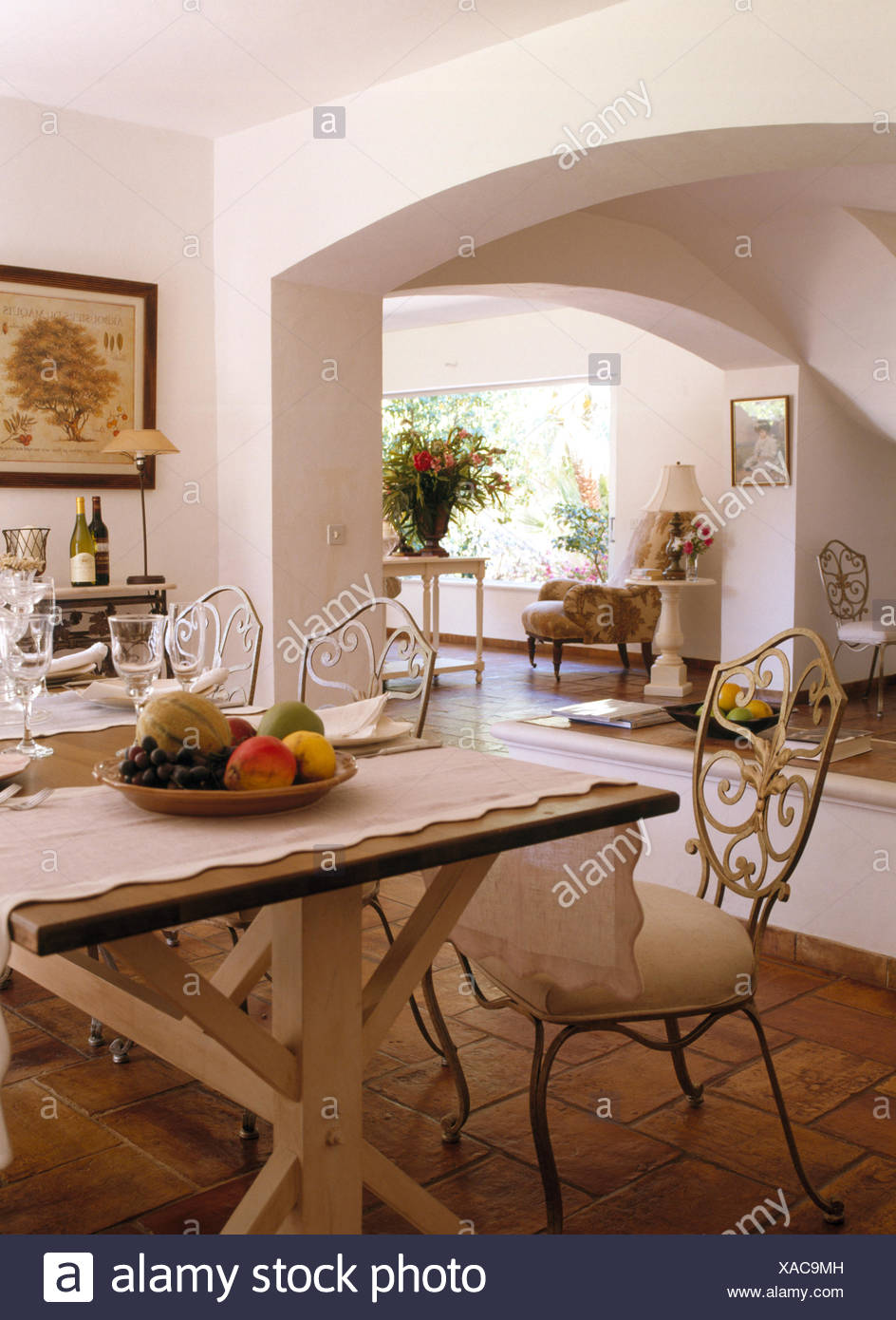 Wrought Iron Chairs At Painted Wooden Table Set For Lunch In French Country Dining Room Stock Photo Alamy