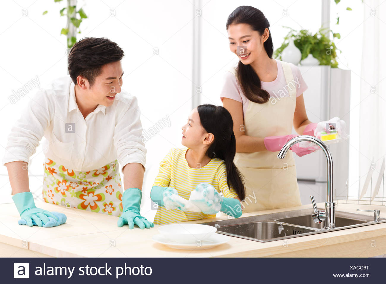 Family doing cleaning-up in kitchen - Stock Image