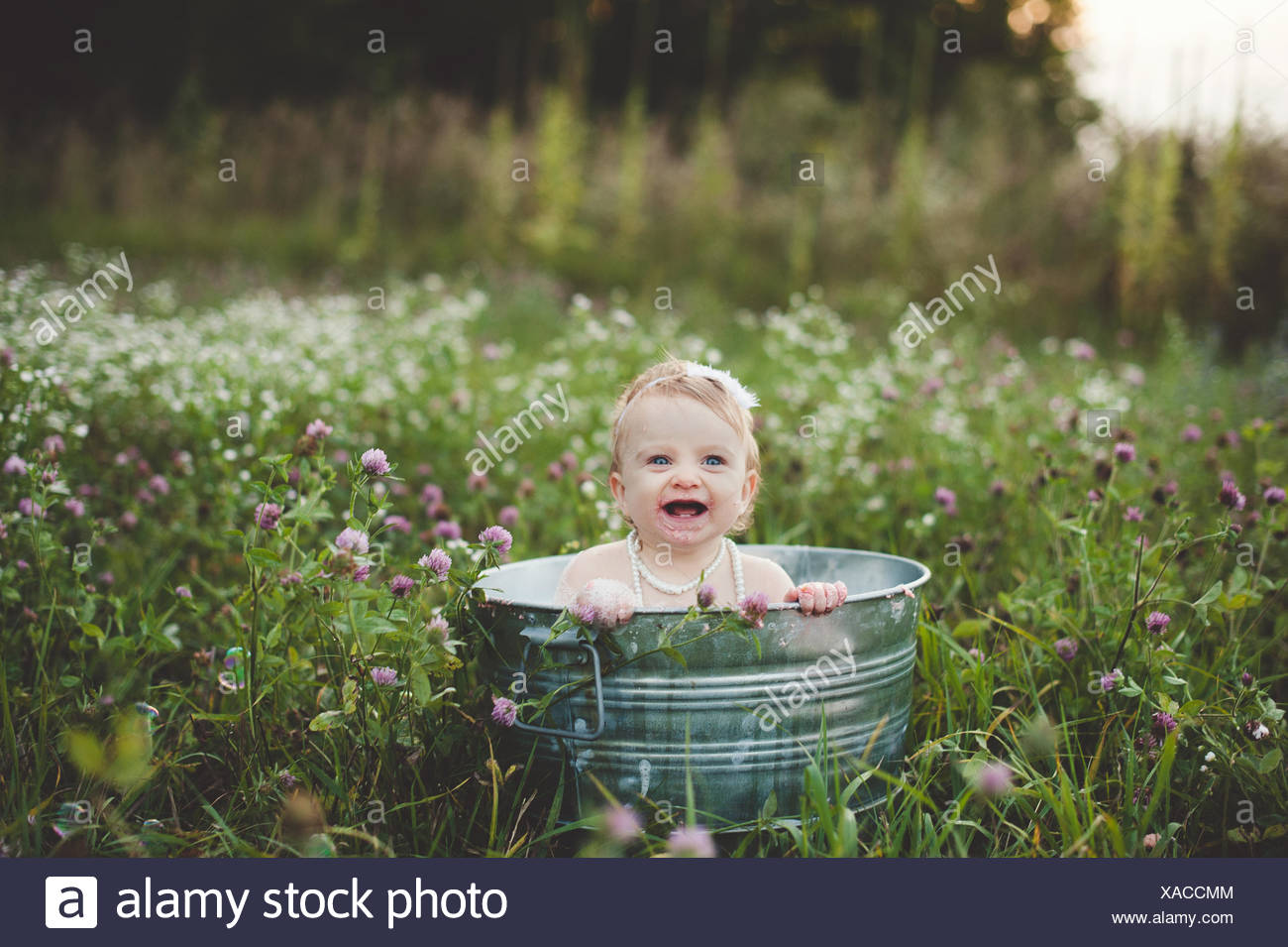 Baby girl bathing in a tin bathtub in a wild flower meadow Stock ...