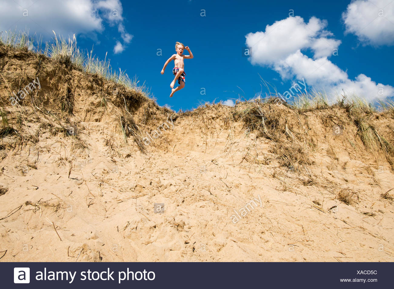 Sweden, Halland, Halmstad, Tylosand, Boy (6-7) jumping from sandy precipice - Stock Image