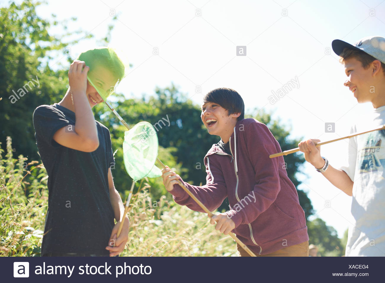 Three boys playing with fishing nets - Stock Image