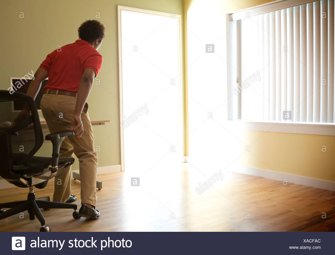Male office worker standing up from chair to investigate light flooding through doorway - Stock Image