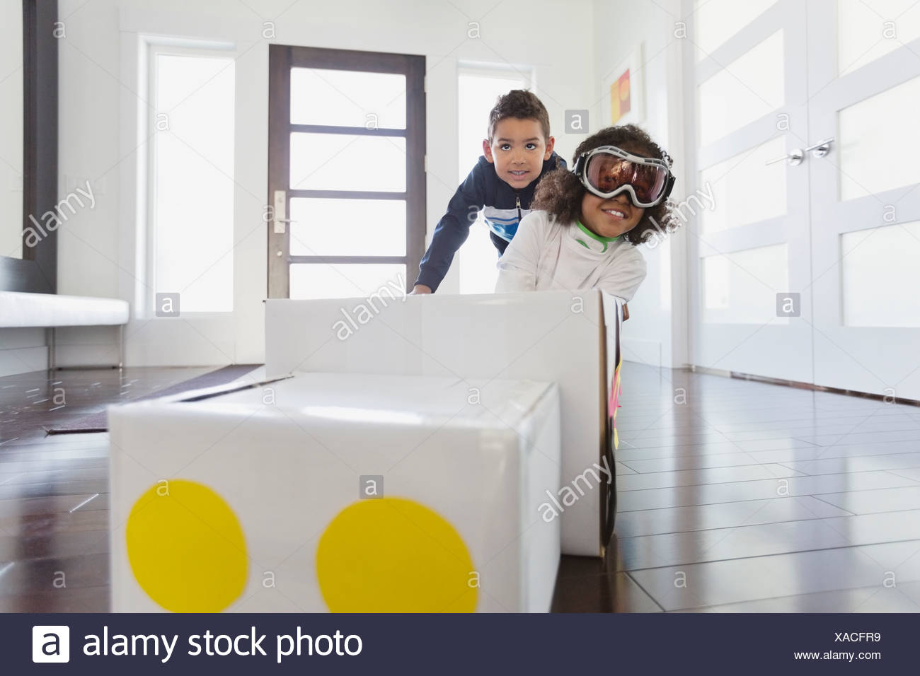 Boy with friend pretending to be race car driver at home - Stock Image