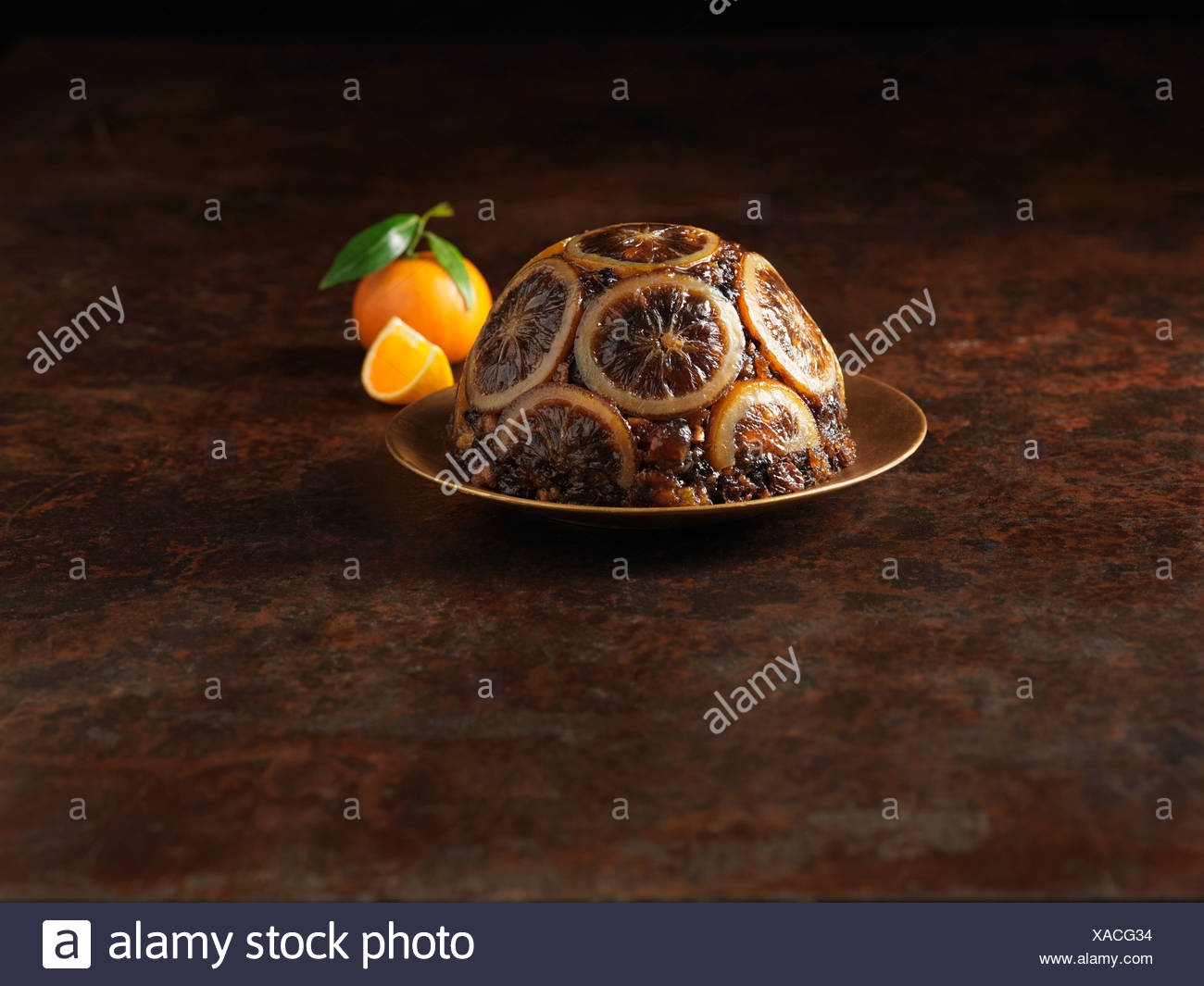Christmas pudding decorated with sliced oranges Stock Photo