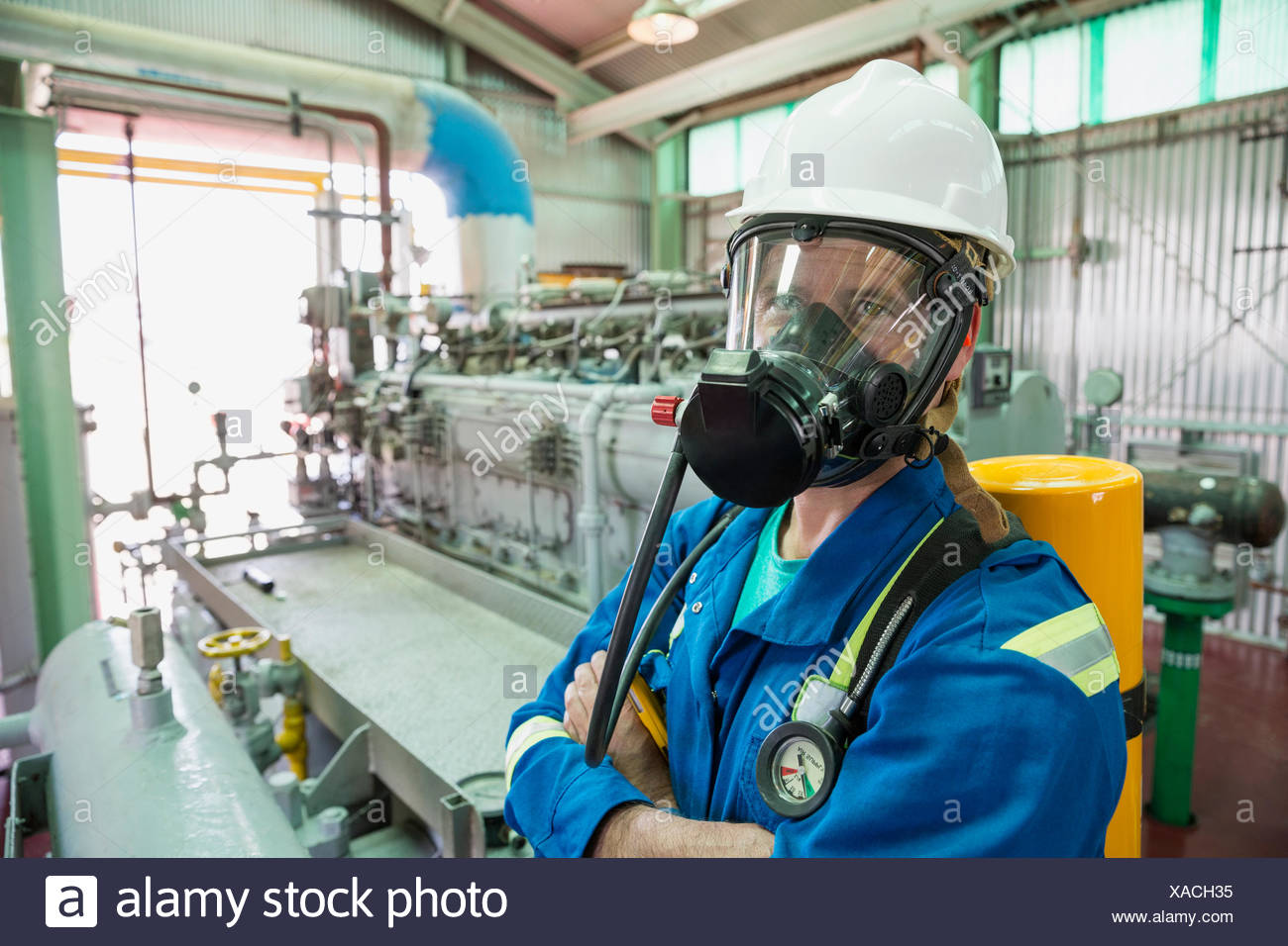 Male worker wearing respirator in gas plant - Stock Image