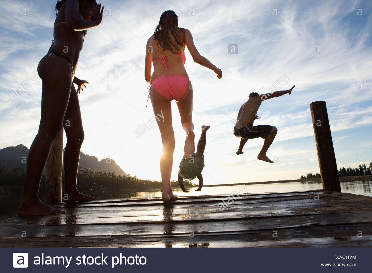 Four young adults in swimwear jumping from jetty into lake at sunset rear view surface level - Stock Image