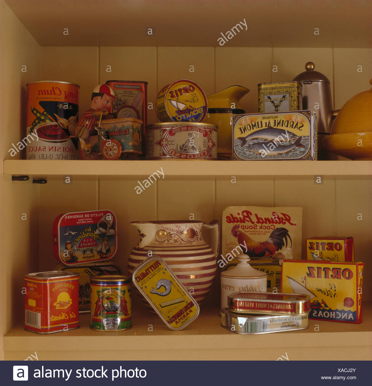Close-up of a collection of vintage tins of food on shelves - Stock Image
