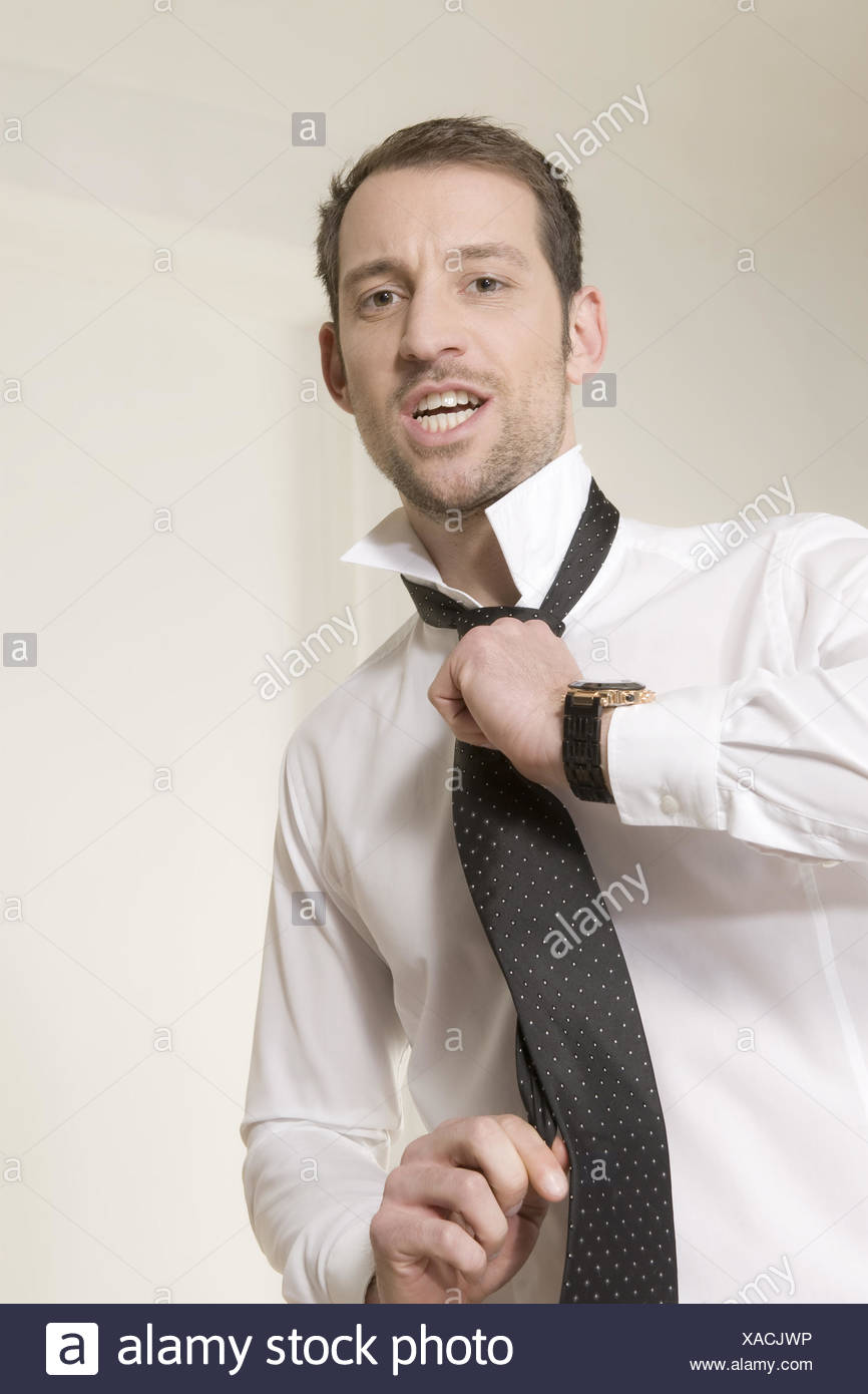 Handsome guy adjusts his tie - Stock Image