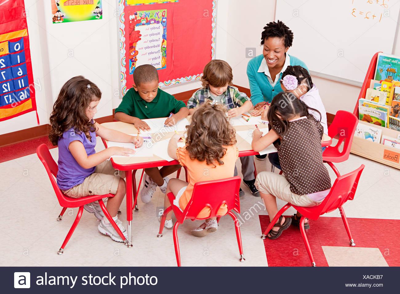 Teacher and children in school art class - Stock Image