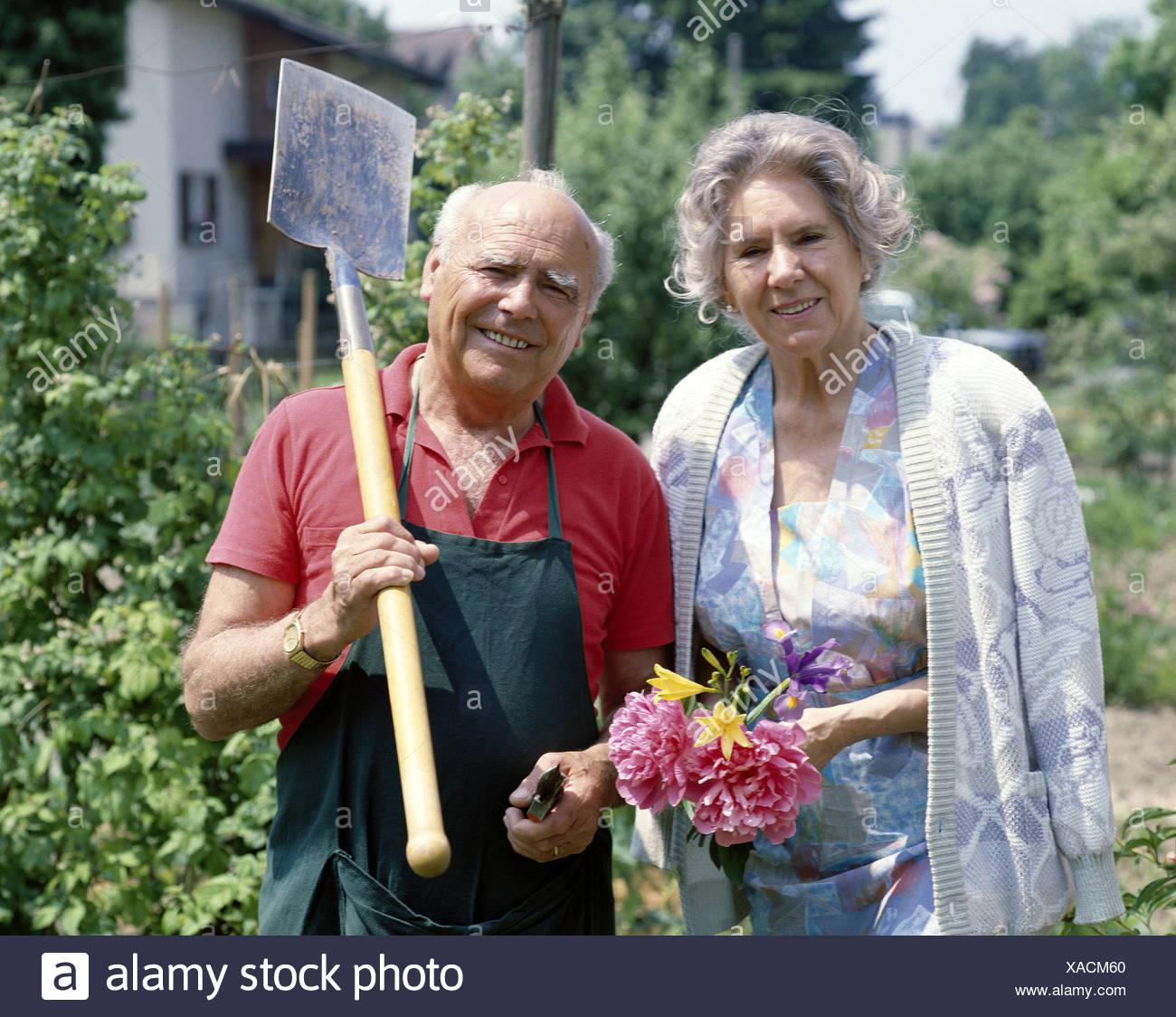working clothes flowers garden amateur gardener pair couple seniors spavins spades - Stock Image