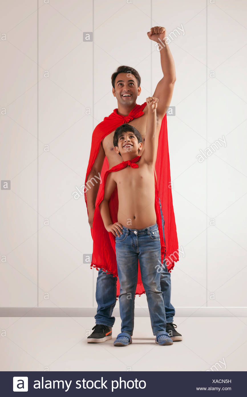 Father and son acting as super heroes - Stock Image