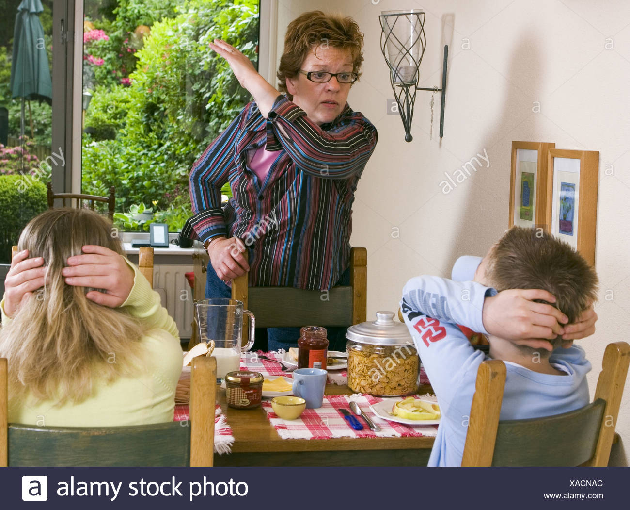 Child abuse at home: Mother smacking her childrenat breakfast table at home and looking very angry. SerieCVS417009 (keyword) - Stock Image