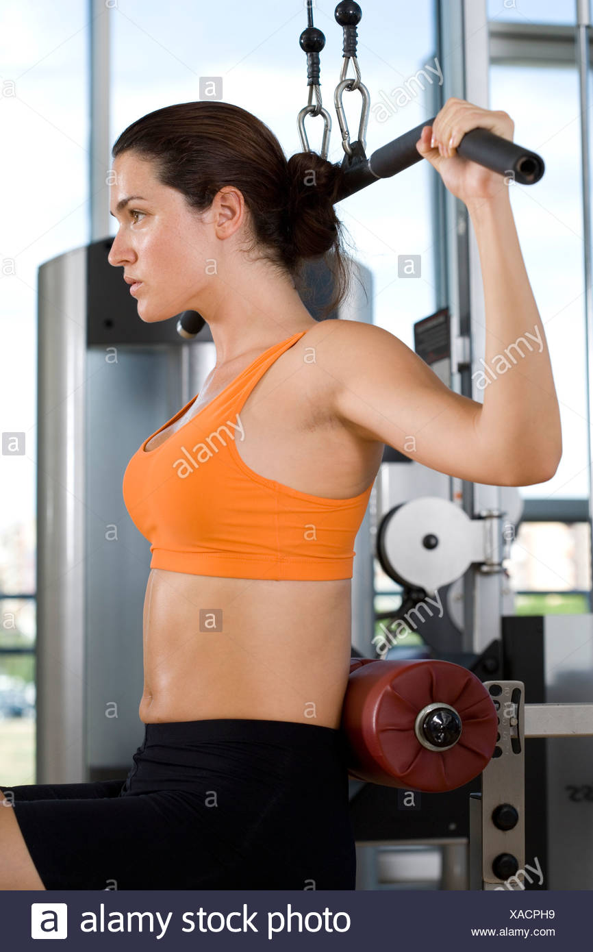 Woman using exercise equipment in gym, side view Stock Photo