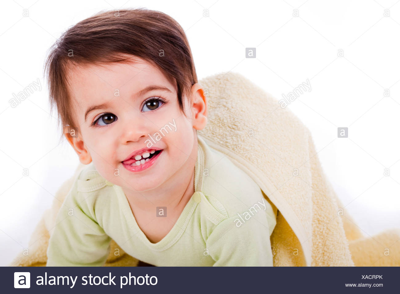 Infant crawling with towel and smiling with tounge out in a white background - Stock Image