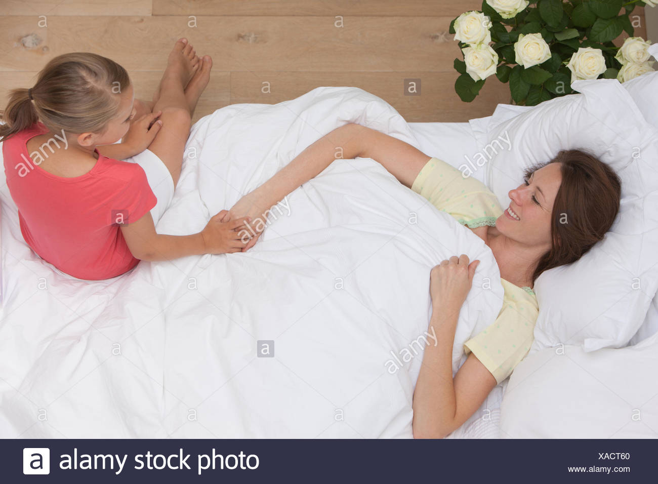 Mother laying in bed  with daughter holding hand - Stock Image