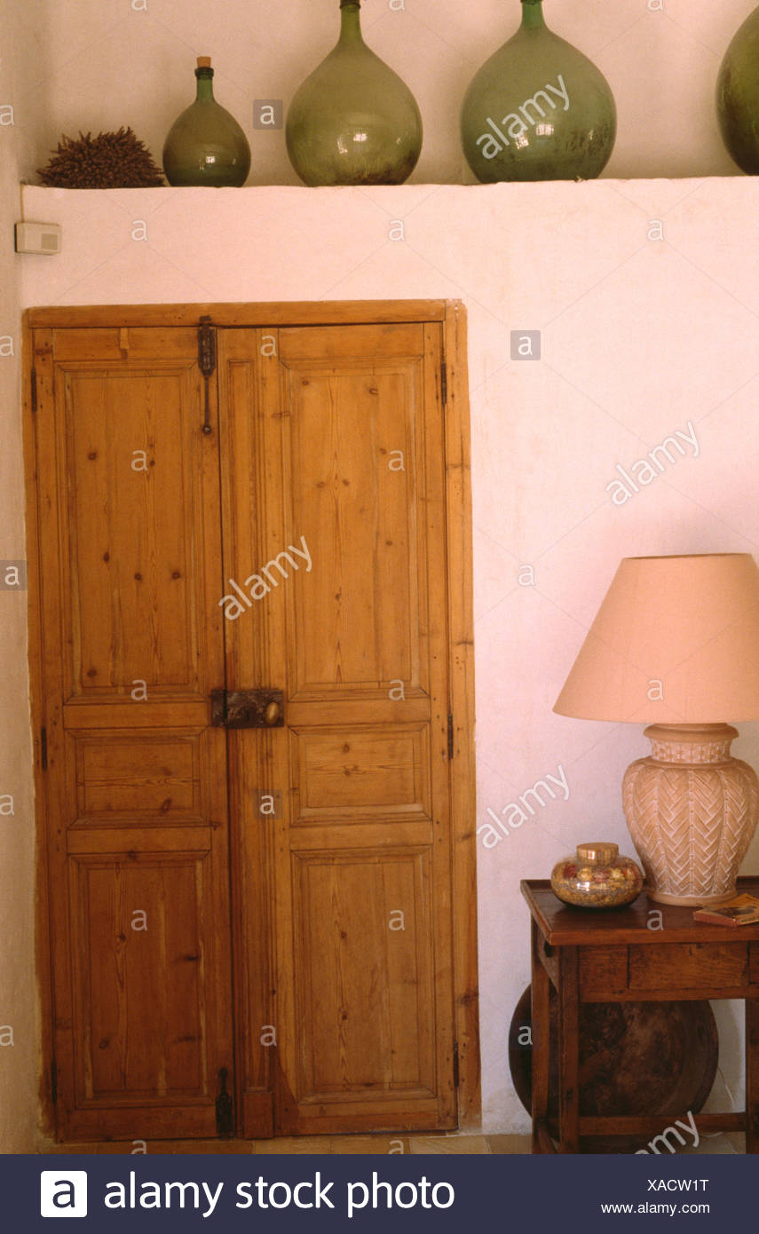 Large glass carboys on recessed shelf above old wooden double doors in cottage hall with cream lamp on small table - Stock Image