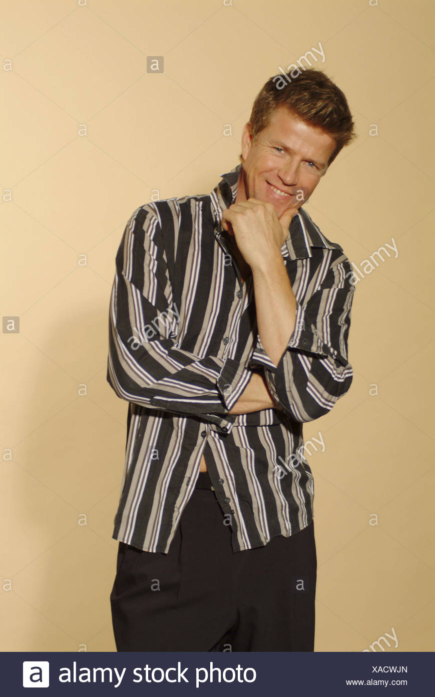 Man, smile young, shirt touched, gesture, detail, 30-40 years, stand, blond, hand, chin, laxly, casually, careless, friendly, balance, self-assurance, selfconsciousness, cool, happy, view camera, clothes, fashionably, fashion, Fashion, style, look, outfit - Stock Image