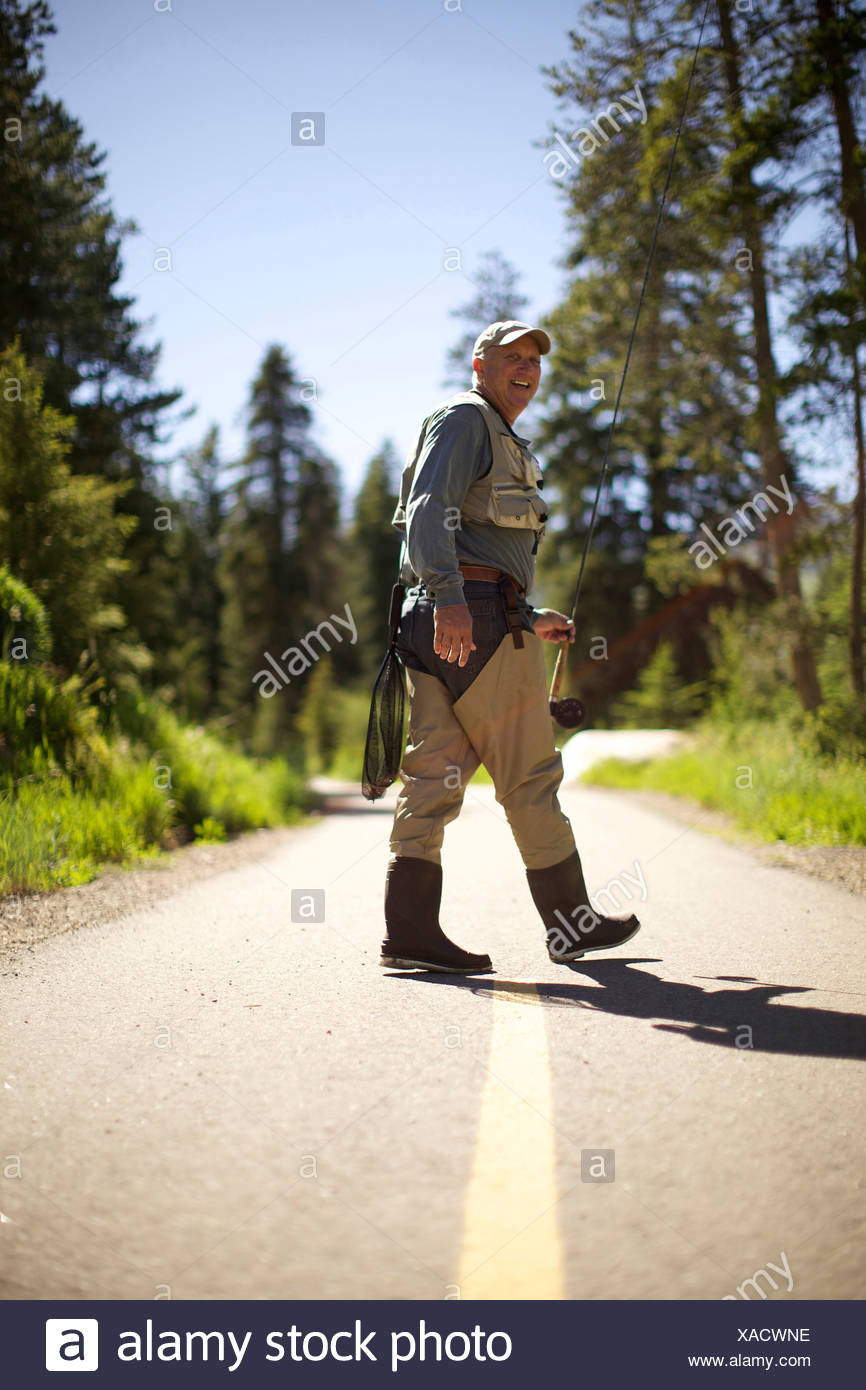 A fisherman holding a fly rod walks away from the camera, looking back and smiling. - Stock Image