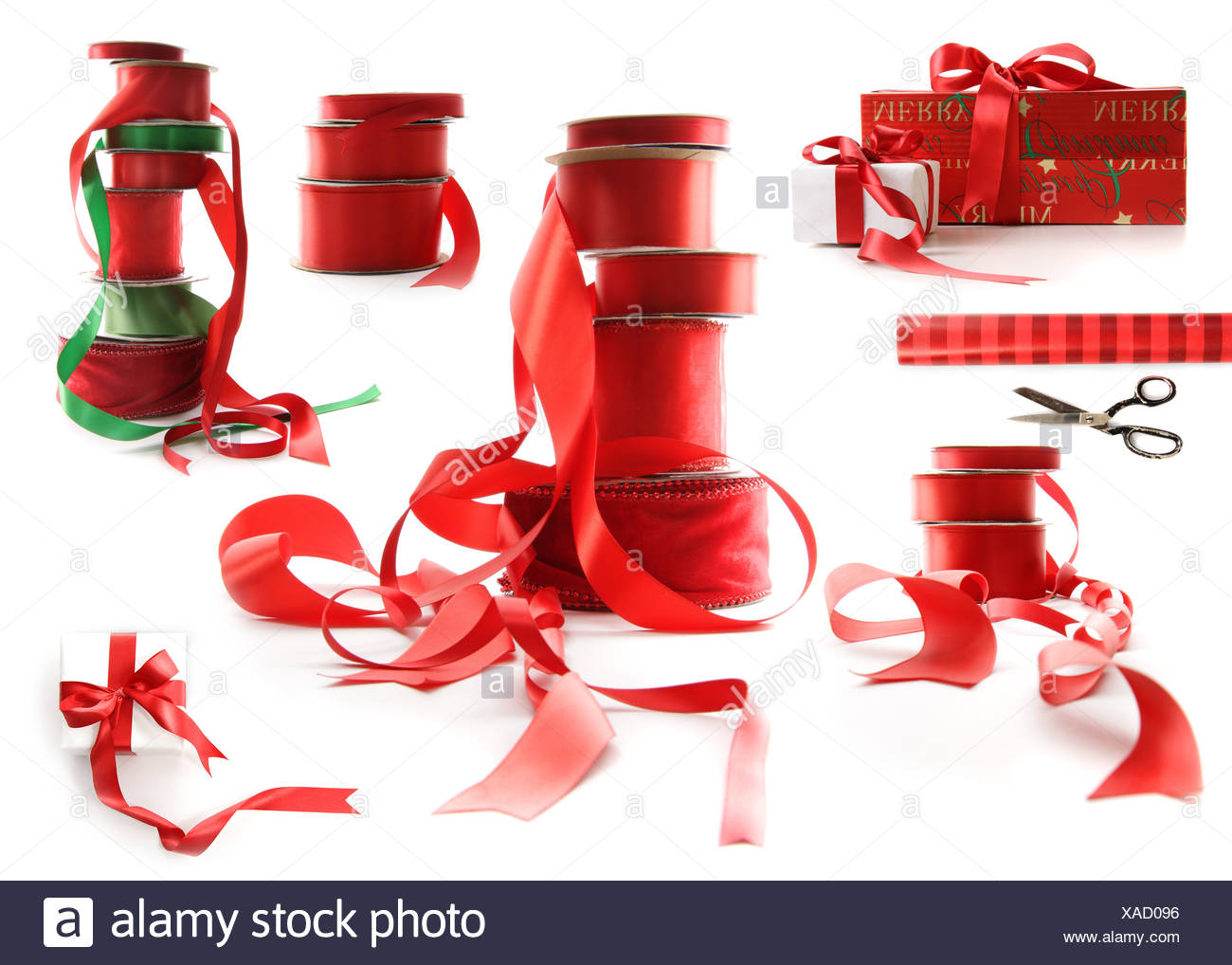 Different sizes of red ribbons and gift wrapped boxes on white background - Stock Image