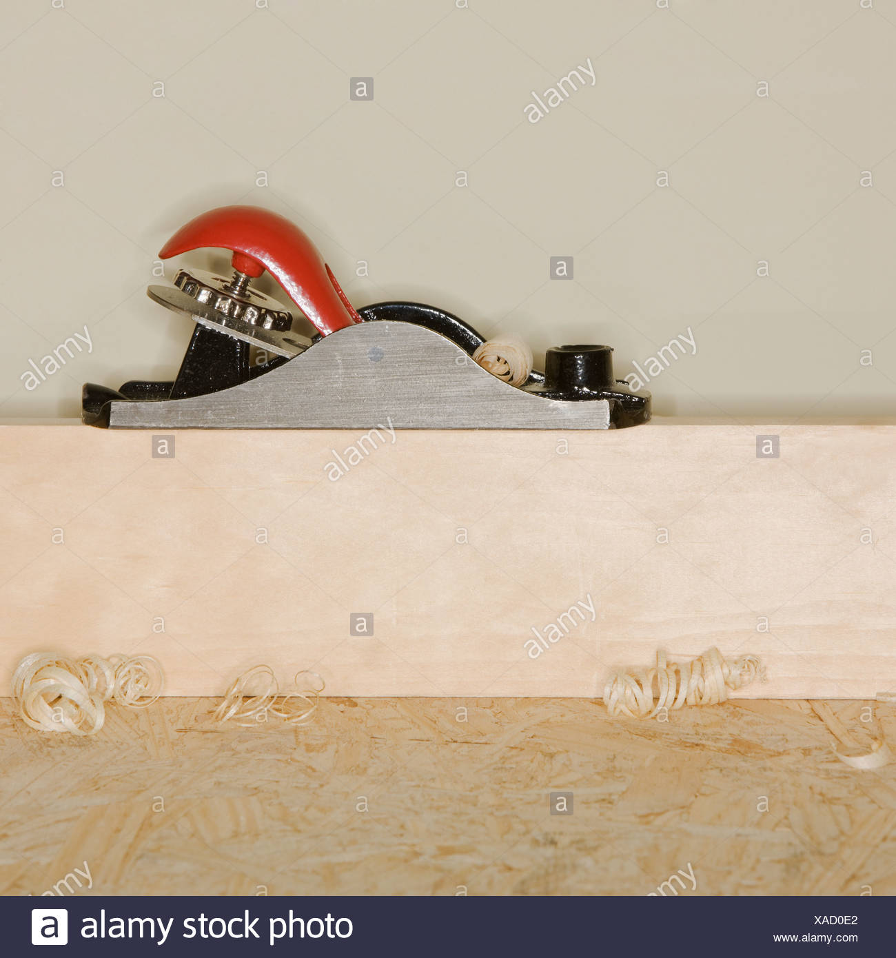 Woodworking plane on block of wood - Stock Image