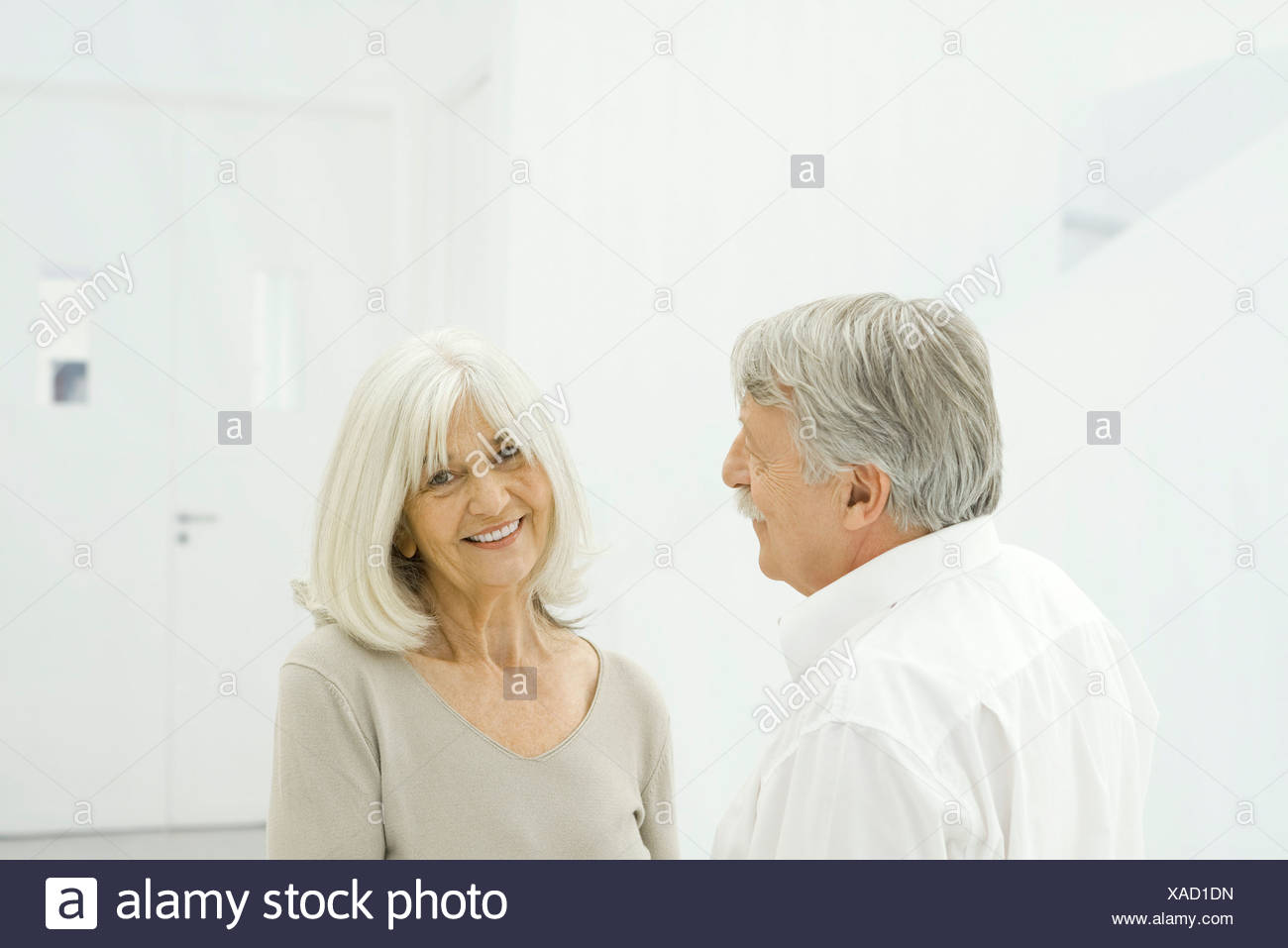 Senior couple standing face to face, woman smiling at camera - Stock Image