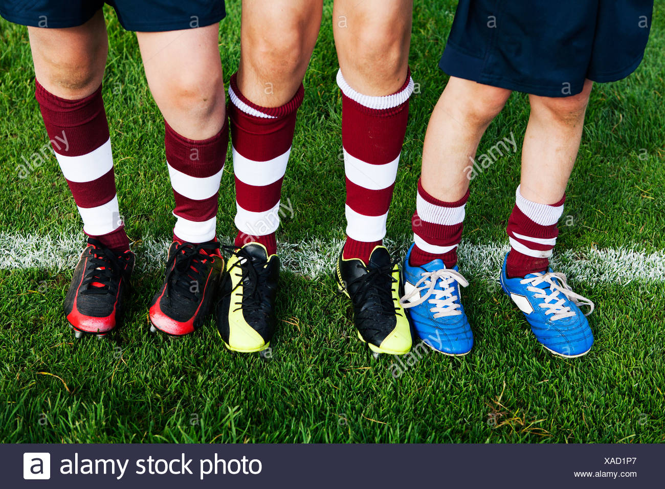 Legs and feet of three schoolboy rugby players - Stock Image