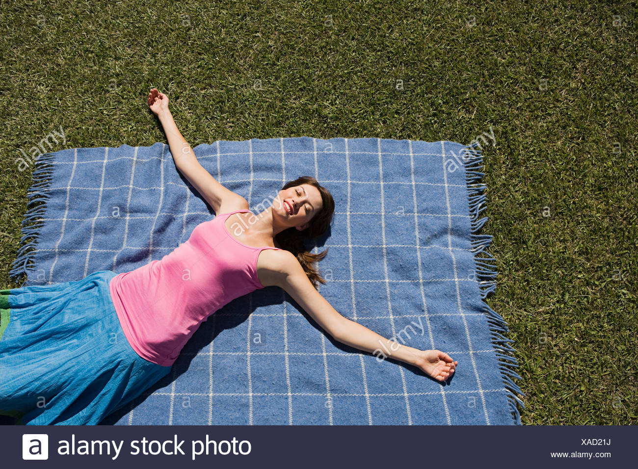 Woman lying on picnic blanket with arms outstretched - Stock Image