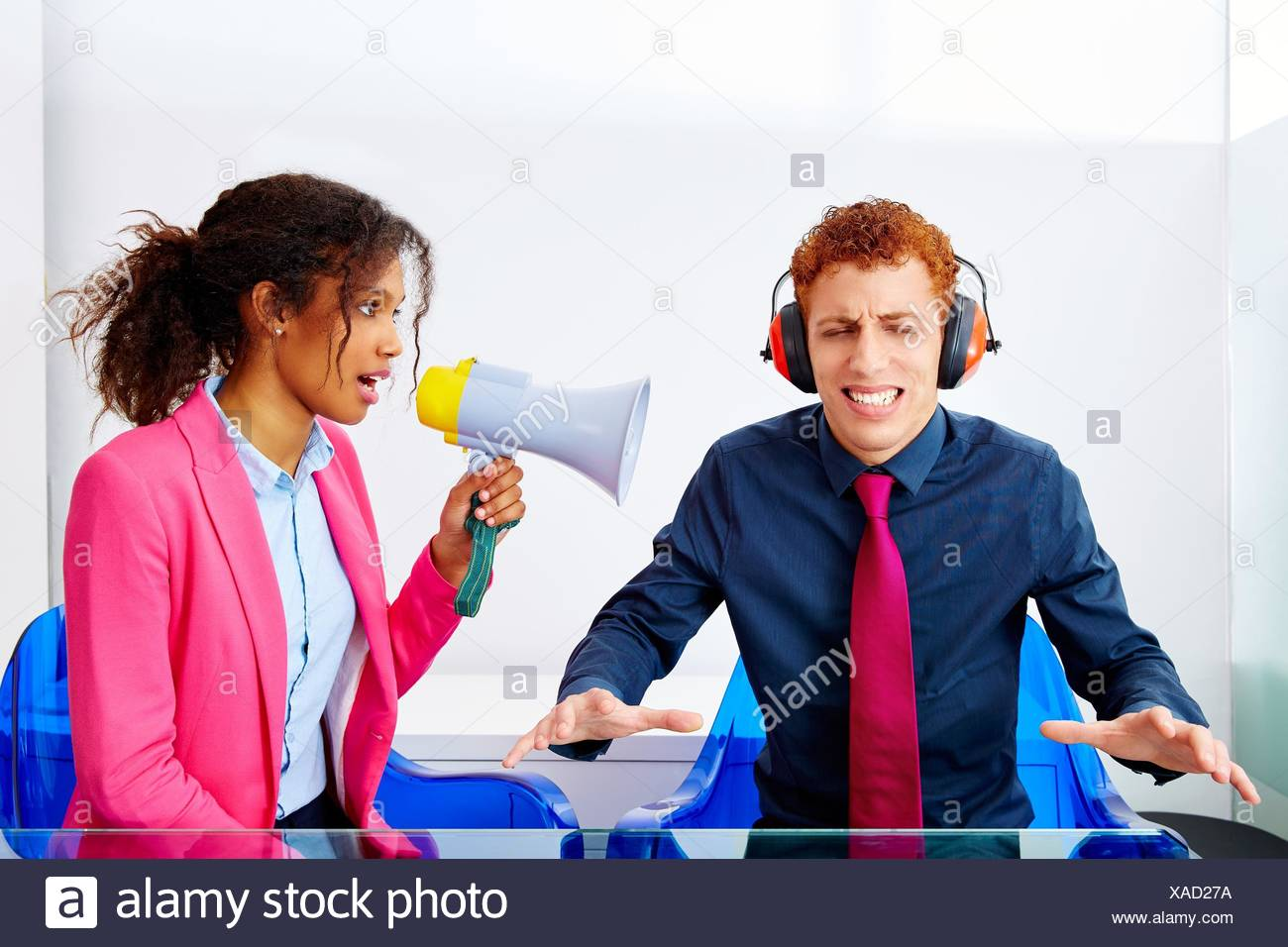 business woman talking in megaphone african ethnicity to young executive. Stock Photo