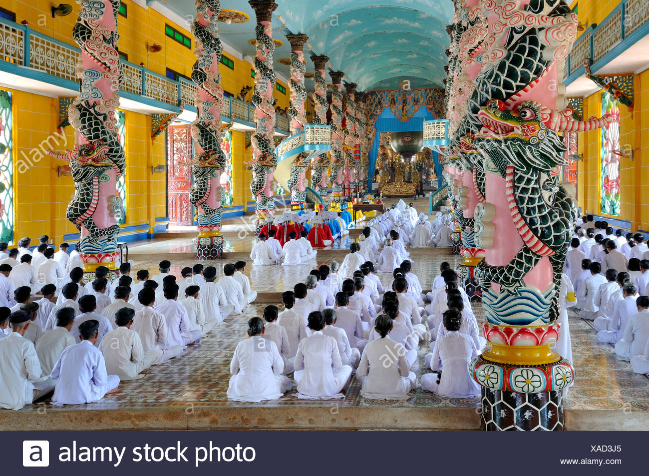 Praying devout men and women, ceremonial midday prayer in the Cao Dai temple, Tay Ninh, Vietnam, Asia - Stock Image