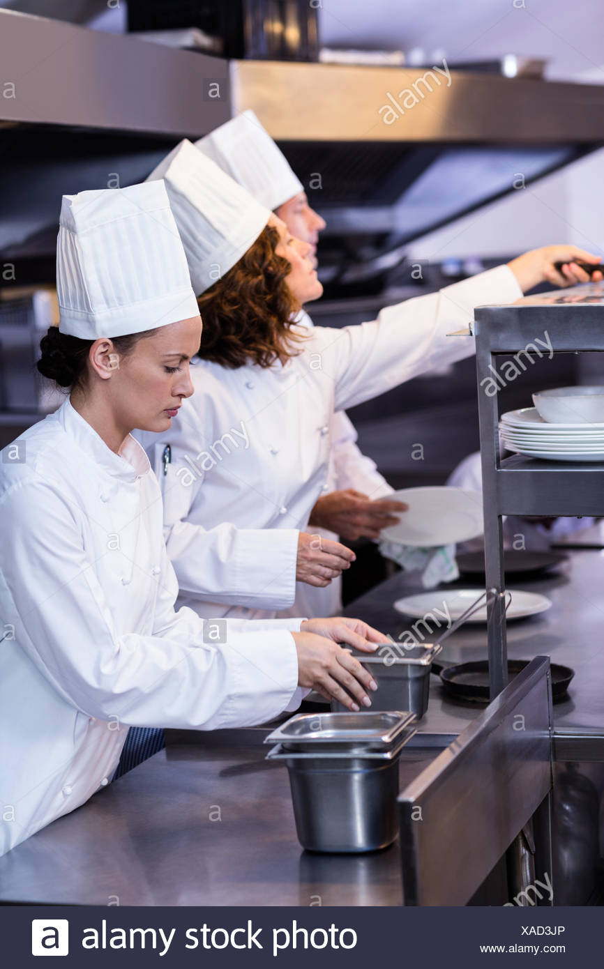Two chefs working at order station in a kitchen - Stock Image