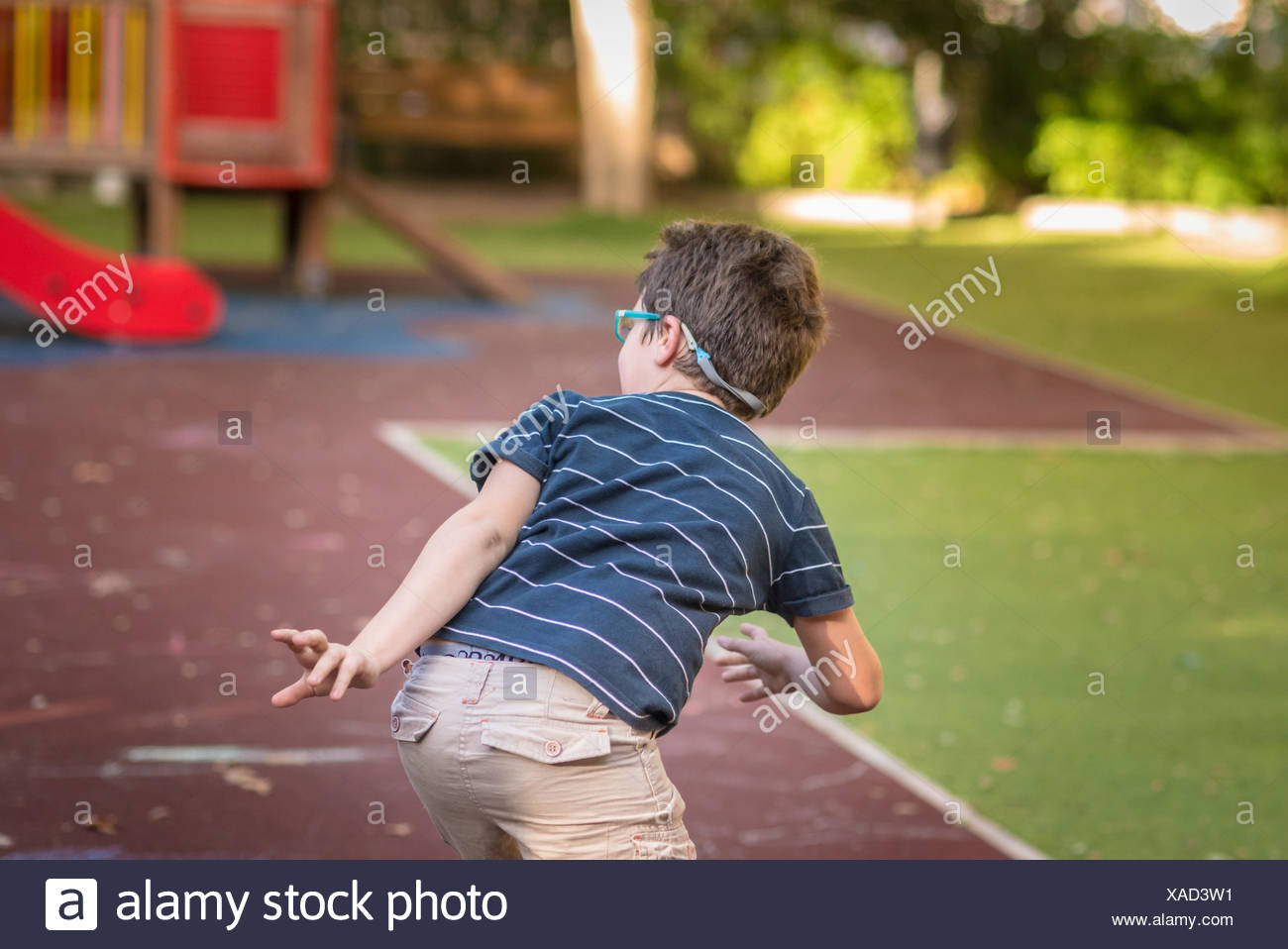 Spain, Valencia, Boy(8-9) playing hide-and-seek in playground - Stock Image