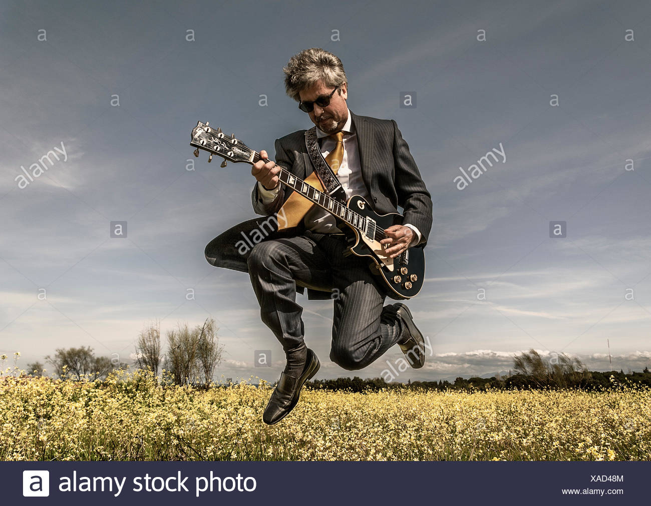 Businessman playing guitar in field - Stock Image