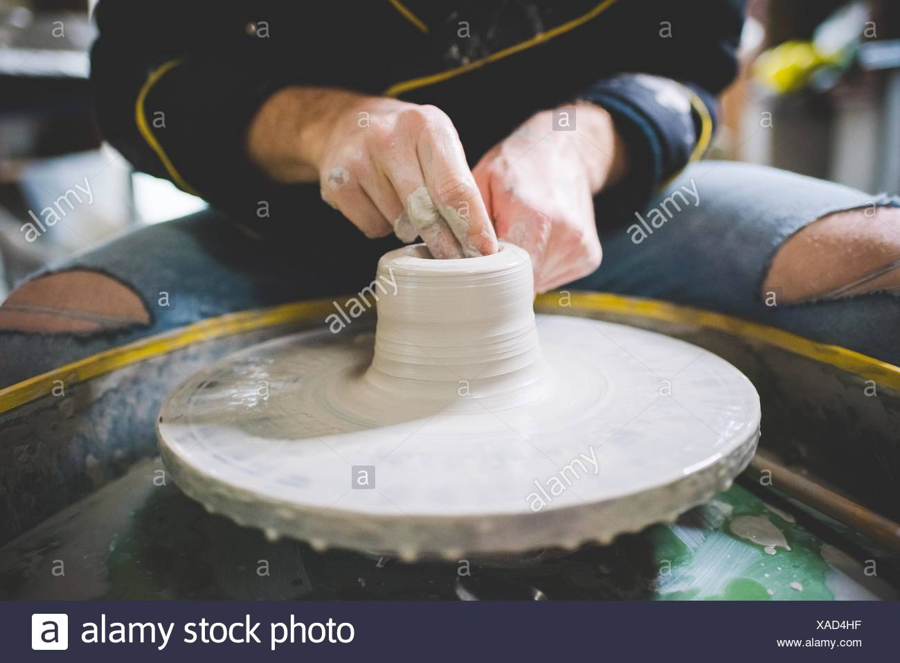 Cropped front view of mid adult man making clay on pottery wheel - Stock Image