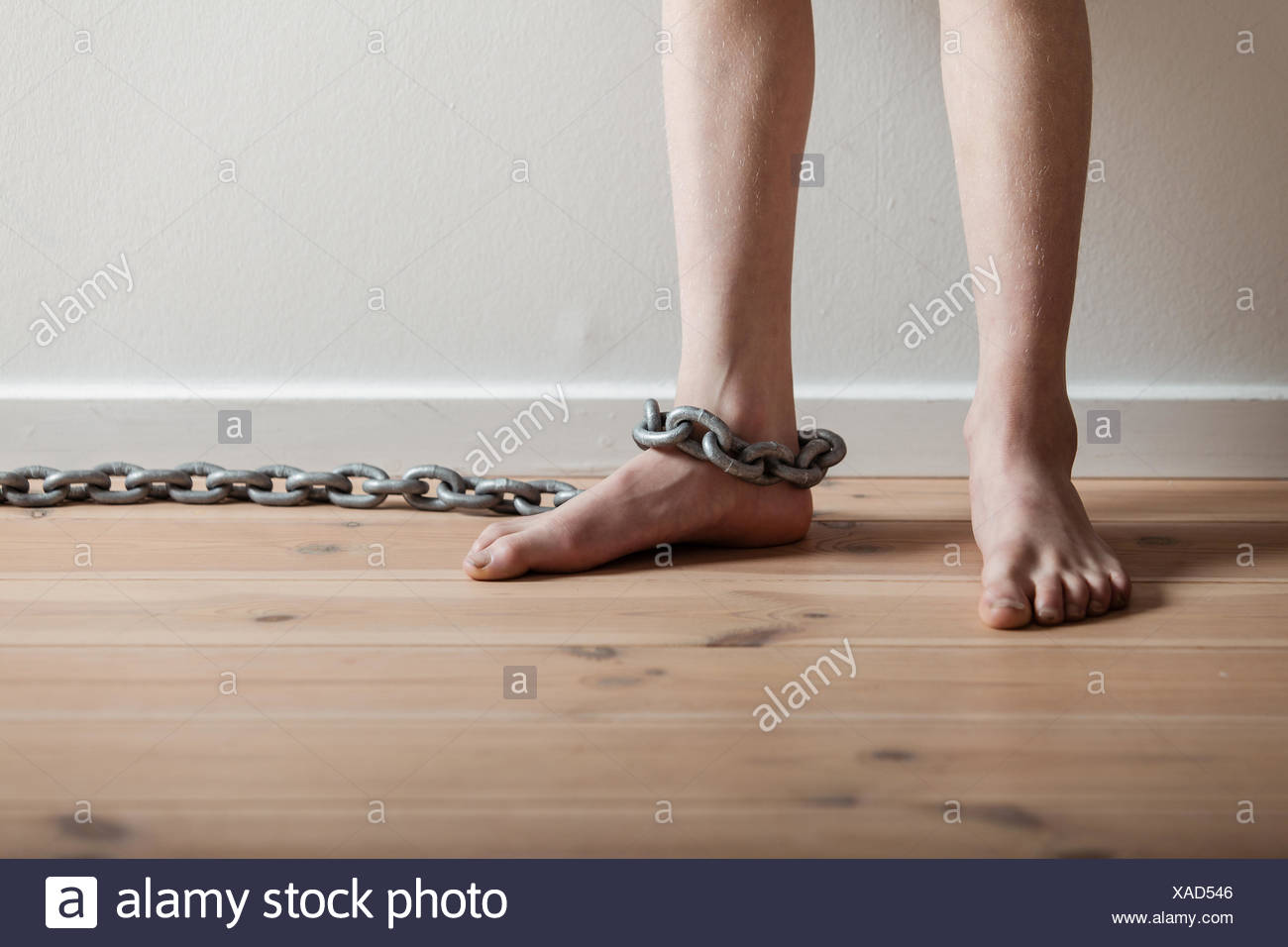 Conceptual Feet of a Boy with Chain Inside a Room - Stock Image