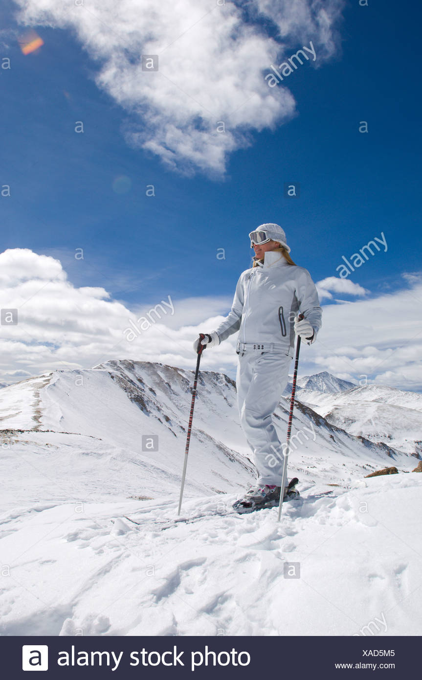 Woman enjoying the view of the Continental Divide in a white ski suit in Colorado. - Stock Image