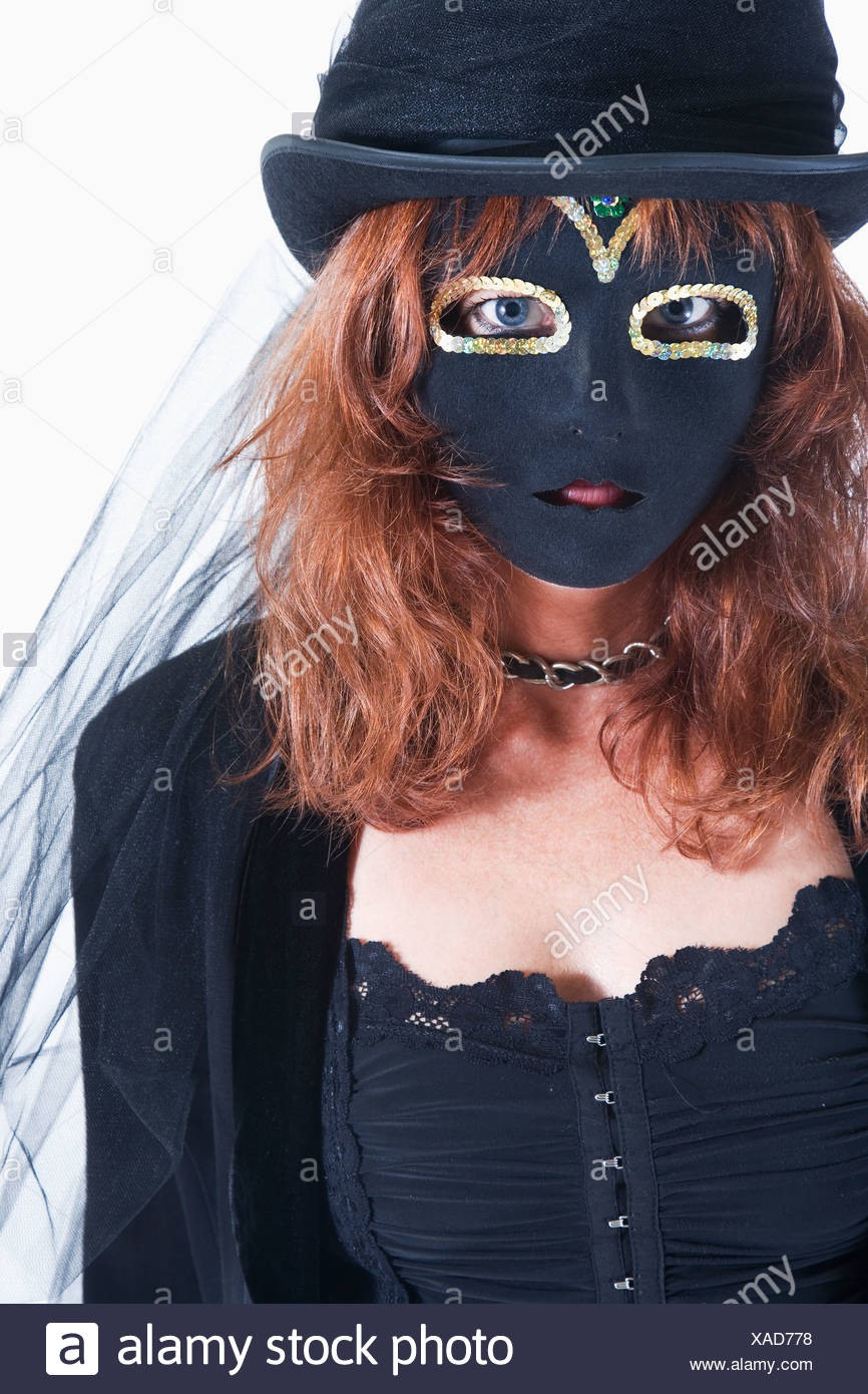 Studio portrait of woman wearing costume and mask - Stock Image