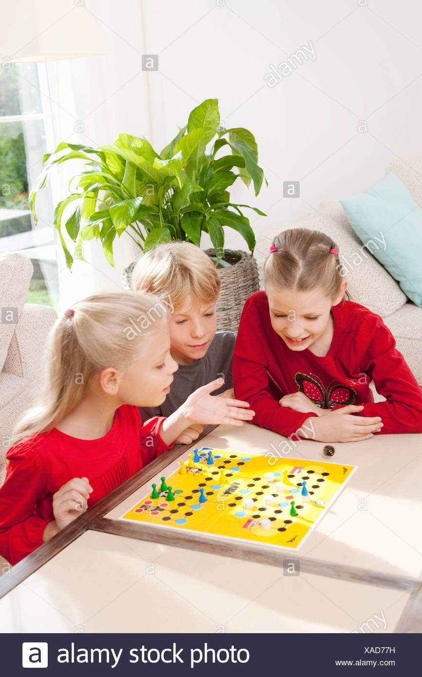 Three children playing a board game - Stock Image