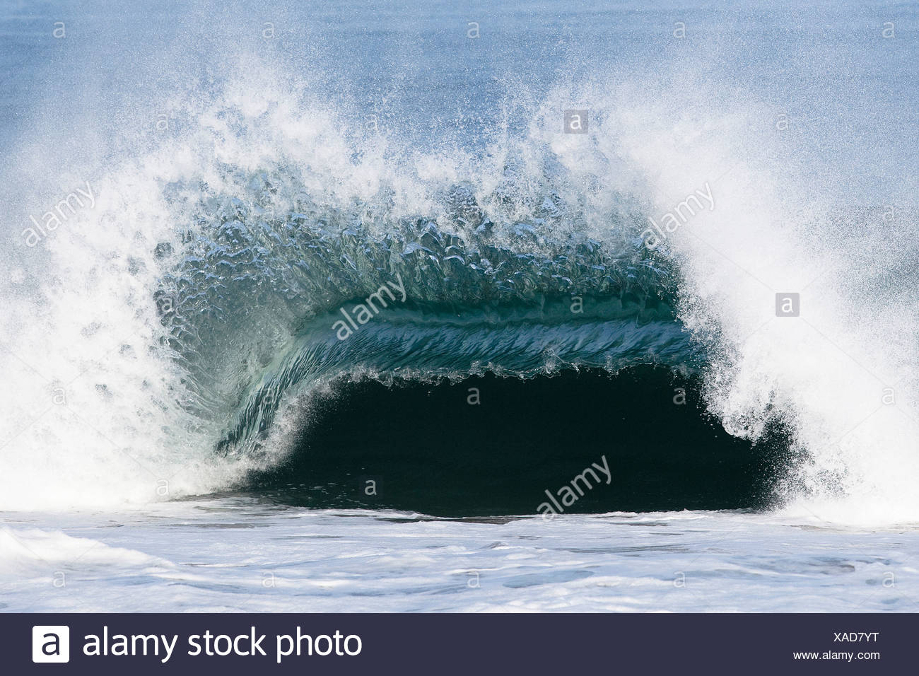 A large wave breaks with force over a shallow sandbar. - Stock Image