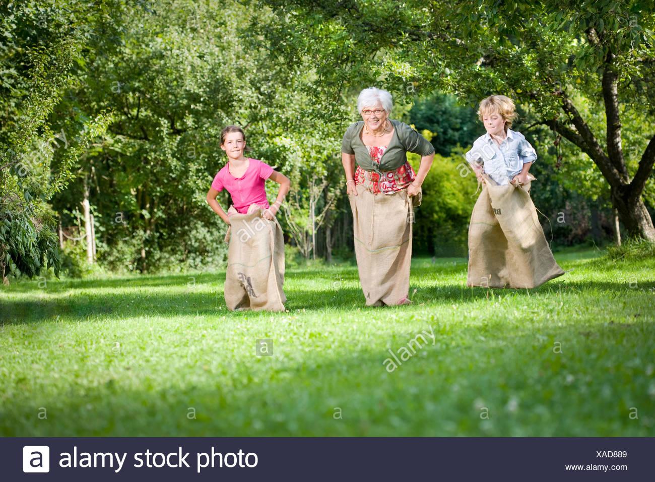 Children sack racing with grandmother - Stock Image