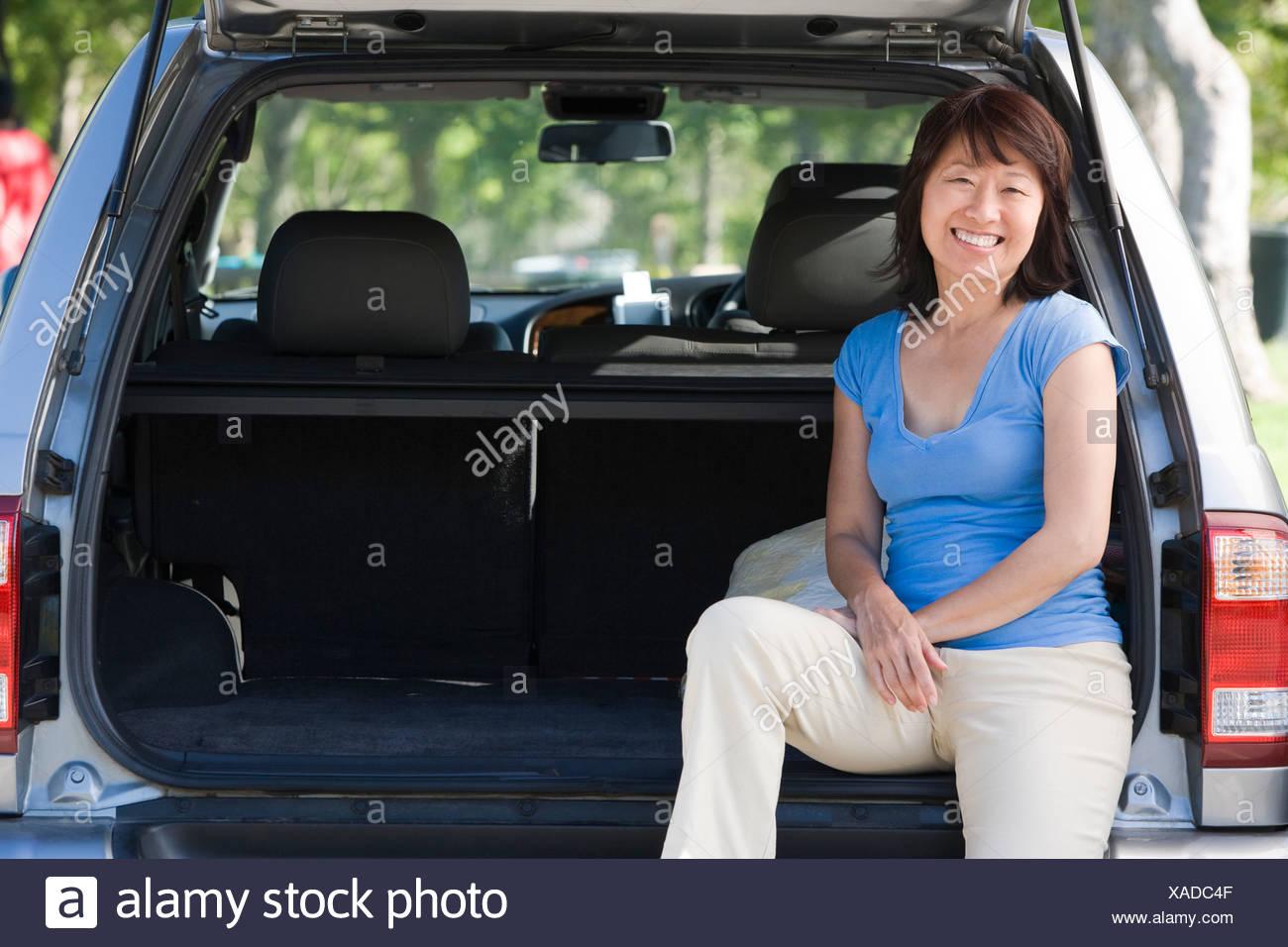 Woman sitting in back of van smiling - Stock Image
