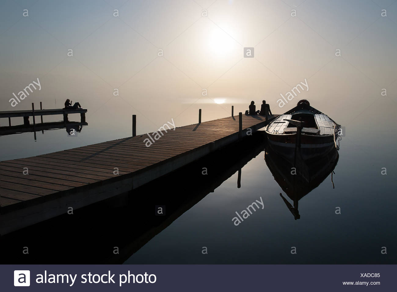 Silhouette of couple sitting at end of jetty by moored boat - Stock Image