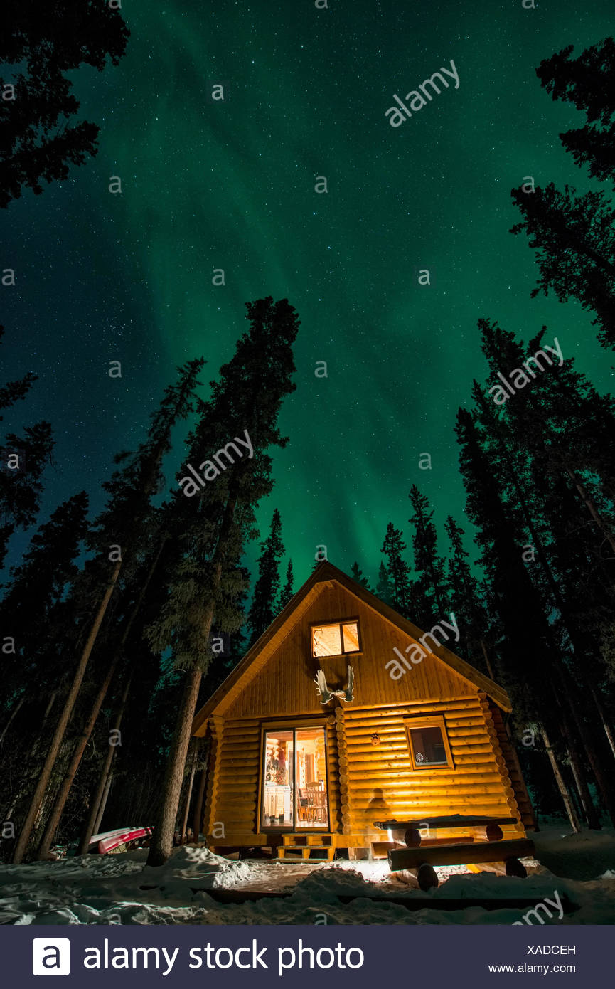 Norther Lights  Aurora Images  in winter in Canada's far north  Aurora Borealis over a log cabin within a boreal forest  Yukon  Canada - Stock Image