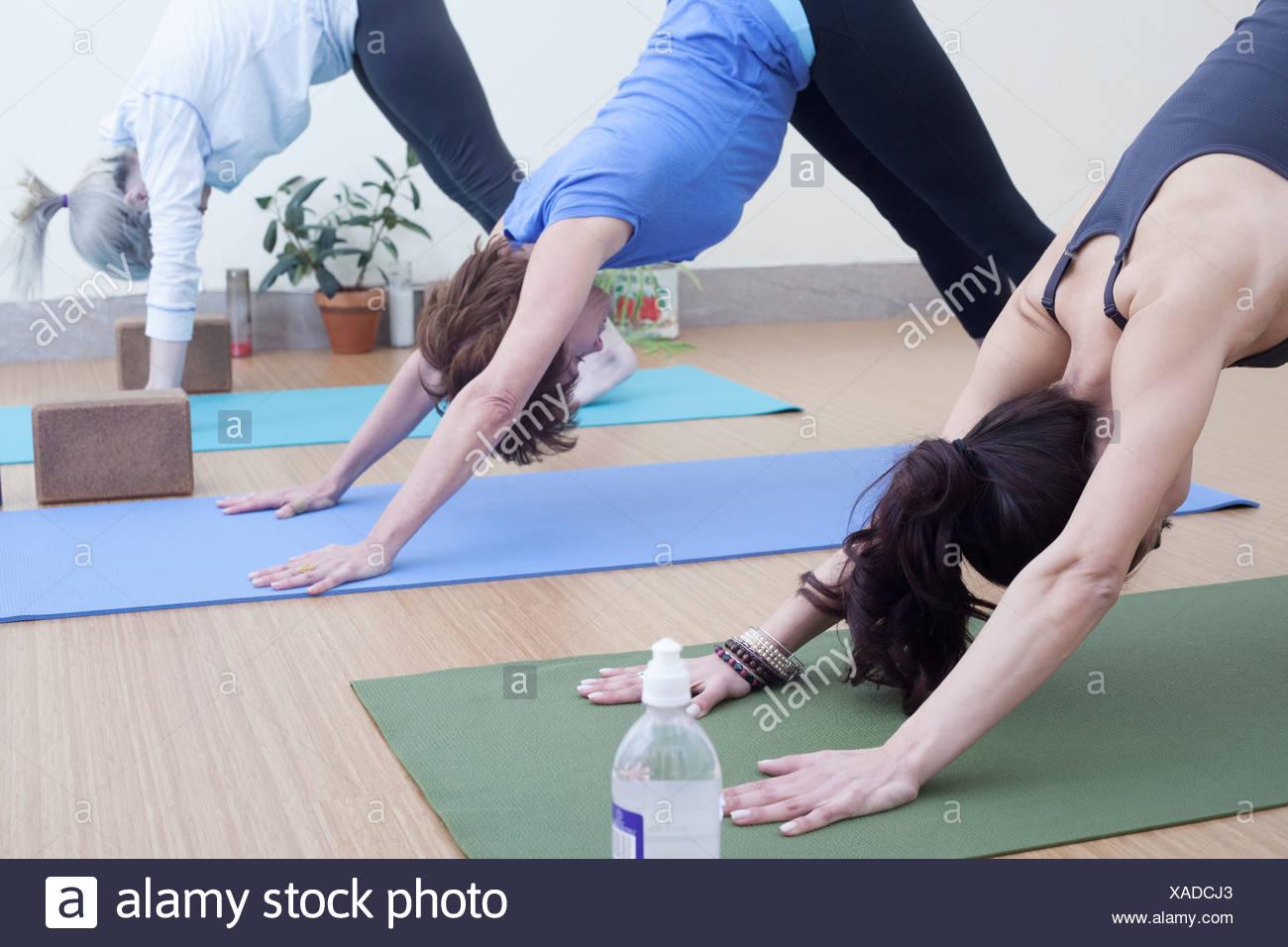Women in downward facing dog pose - Stock Image
