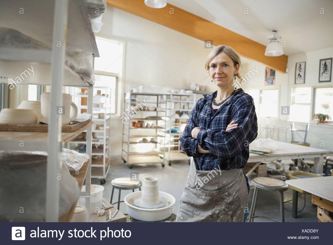 Portrait of confident woman in pottery studio - Stock Image