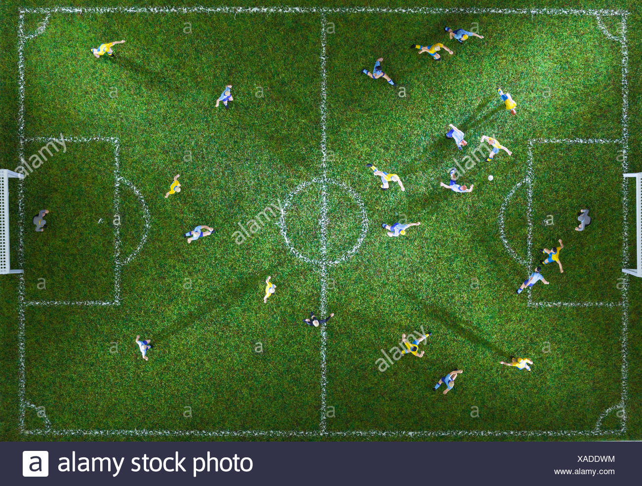 Miniature figurines of two soccer teams playing a soccer match, directly above - Stock Image