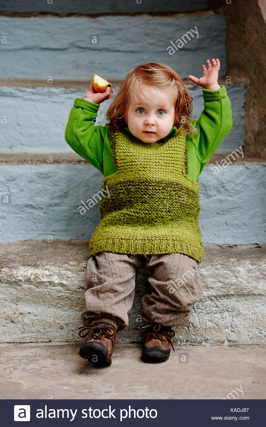 Young girl sitting on stone steps, portrait - Stock Image