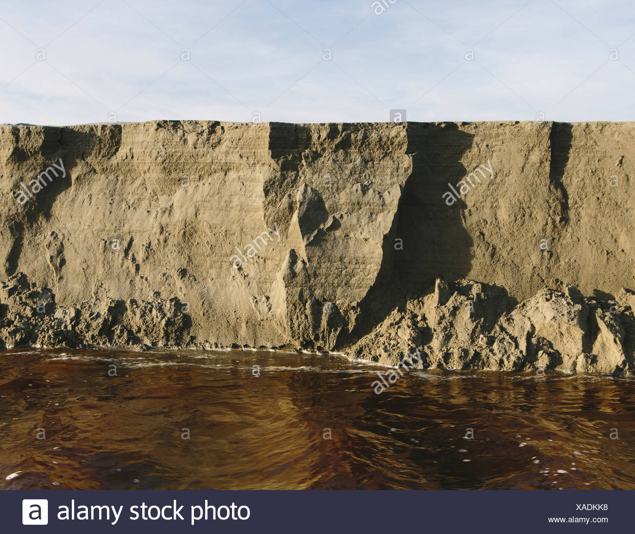 Eroding sand in fast moving water along intertidal area of beach Ocean Park - Stock Image