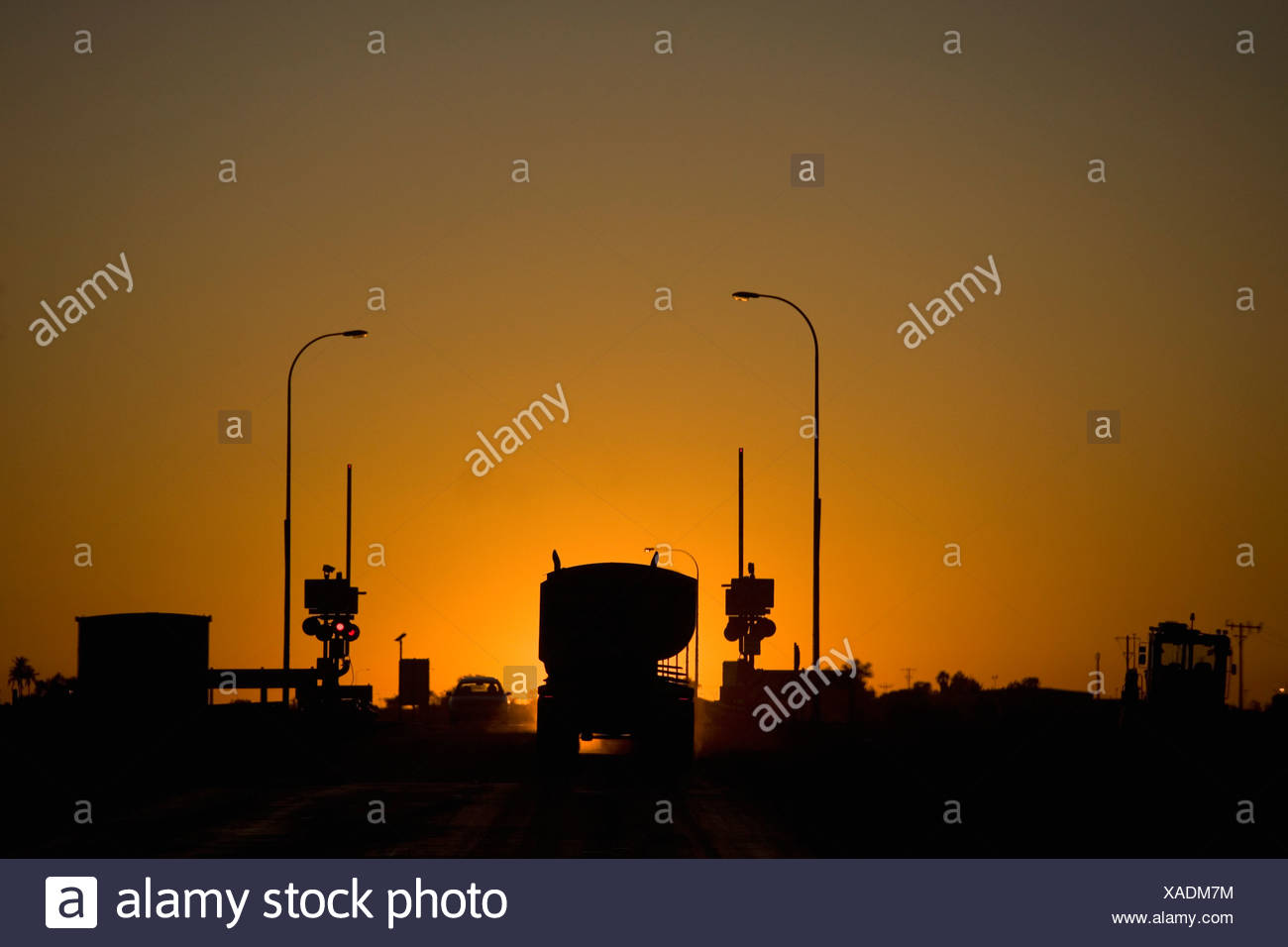 A freight truck and car stopped at a railroad crossing silhouetted against the setting sun - Stock Image
